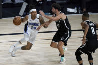 Orlando Magic's Markelle Fultz (20) heads to the basket as Brooklyn Nets' Joe Harris (12) and Timothe Luwawu-Cabarrot (9) defend during the first half of an NBA basketball game Friday, July 31, 2020, in Lake Buena Vista, Fla. (AP Photo/Ashley Landis, Pool)