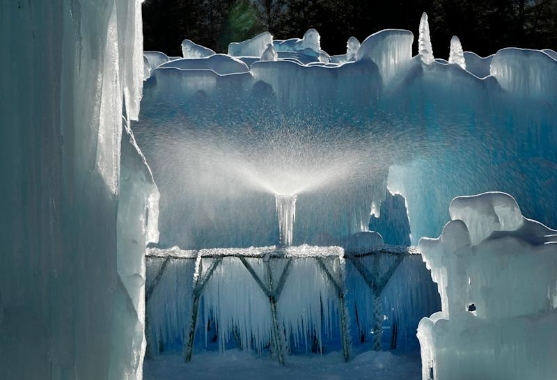 A sprinkler sprays a fine mist over a metal rack to grow icicles at Ice Castles in North Woodstock, N.H. Ice artists will harvest the icicles and use them to grow the castles' walls. (Photo: Robert F. Bukaty/AP)