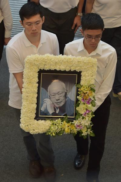 Grandchildren of Singapore's former prime minister Lee Kuan Yew carry his portrait during a funeral procession at the University Cultural Center in Singapore on March 29, 2015 (AFP Photo/Adek Berry)