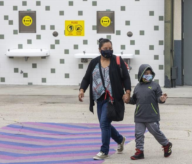 """Los Angeles, CA - July 26: First grade student Daniel Cano, 5, and his mom, Sonia Cano, walk past COVID-19 safety precaution/ social distancing and hand washing signs at the drinking fountain at a L.A. Unified """"meet and greet"""" with its medical advisors as they answer questions and present the safety preparations at Euclid Avenue Elementary School Monday, July 26, 2021 in Los Angeles, CA. Parents have until Friday to choose whether to return their children to in-person classes or remain online in the fall. The first day of school is in mid-August. (Allen J. Schaben / Los Angeles Times)"""