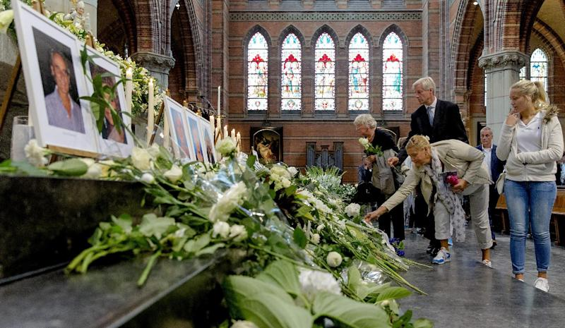 People place flowers under near photographs of MH17 victims on August 17, 2014 during a memorial service in Hilversum, Netherlands