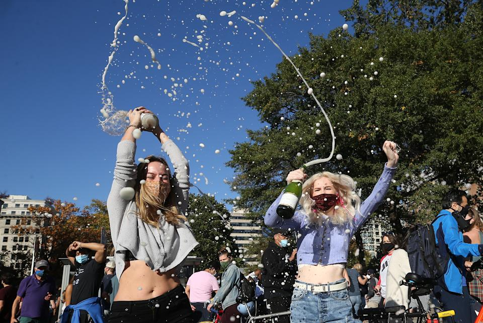Two women in Washington spray sparkling wine in a street as they celebrate after the media announcement that Democratic Party nominee Joe Biden has won. Source: Getty