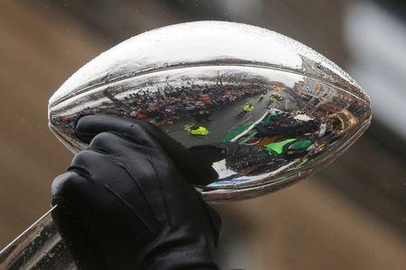 The crowds of fans lining the street are reflected in one of the team's five Vince Lombardi trophies carried by the New England Patriots players through the streets of Boston after winning Super Bowl LI, in Boston, Massachusetts, U.S. February 7, 2017.   REUTERS/Brian Snyder