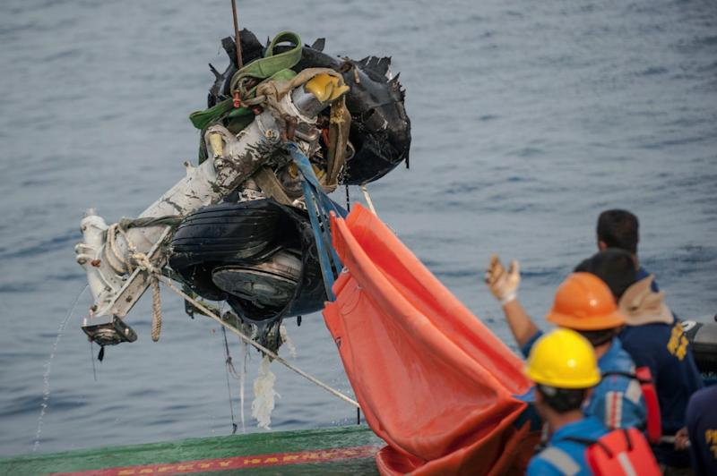 Rescuers use a crane to retrieve part of the landing gears of the crashed Lion Air jet (AP)
