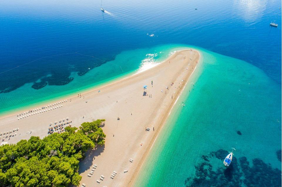 """<p>Unlike the aptly named Pig Beach, <a href=""""https://www.tripadvisor.com/Attraction_Review-g303802-d550460-Reviews-Zlatni_Rat_Beach_Golden_Horn-Bol_Brac_Island_Split_Dalmatia_County_Dalmatia.html"""" rel=""""nofollow noopener"""" target=""""_blank"""" data-ylk=""""slk:Zlatni Rat Beach"""" class=""""link rapid-noclick-resp"""">Zlatni Rat Beach</a> is not home to a beloved colony of rats. Part of what makes Zlatni Rat Beach special is its uniquely-shaped coastline, which juts like an elbow—or """"<a href=""""https://www.bolcroatia.com/bol-beaches/zlatni-rat-beach/"""" rel=""""nofollow noopener"""" target=""""_blank"""" data-ylk=""""slk:Golden Horn"""" class=""""link rapid-noclick-resp"""">Golden Horn</a>"""" (as it's also referred to) out into the Adriatic Sea. Ranging from clear to deep, deep blue—with a turquoise transition—the water is as gorgeous as the coast is crooked.</p>"""
