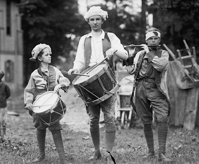 <p>Three boys in Colonial garb march with instruments at a Fourth of July celebration, 1922. (Photo: Buyenlarge/Getty Images) </p>