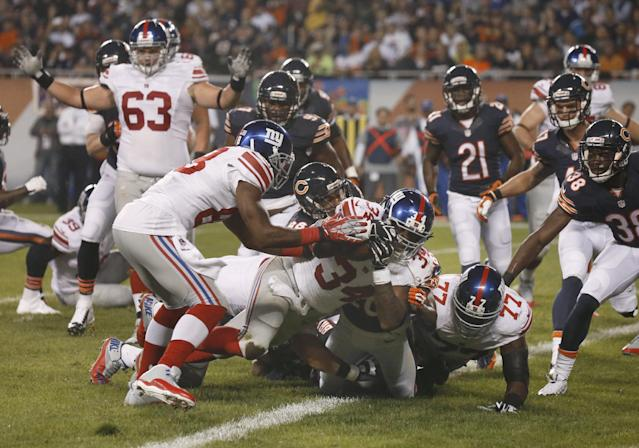New York Giants running back Brandon Jacobs (34) rolls into the end zone for a touchdown in the first half of an NFL football game against the Chicago Bears, Thursday, Oct. 10, 2013, in Chicago. (AP Photo/Charles Rex Arbogast)