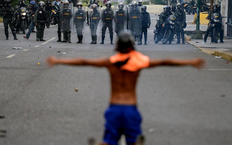 Opposition activists clash with riot police during a protest against President Nicolas Maduro in Caracas on April 26, 2017 - Credit: FEDERICO PARRA/AFP