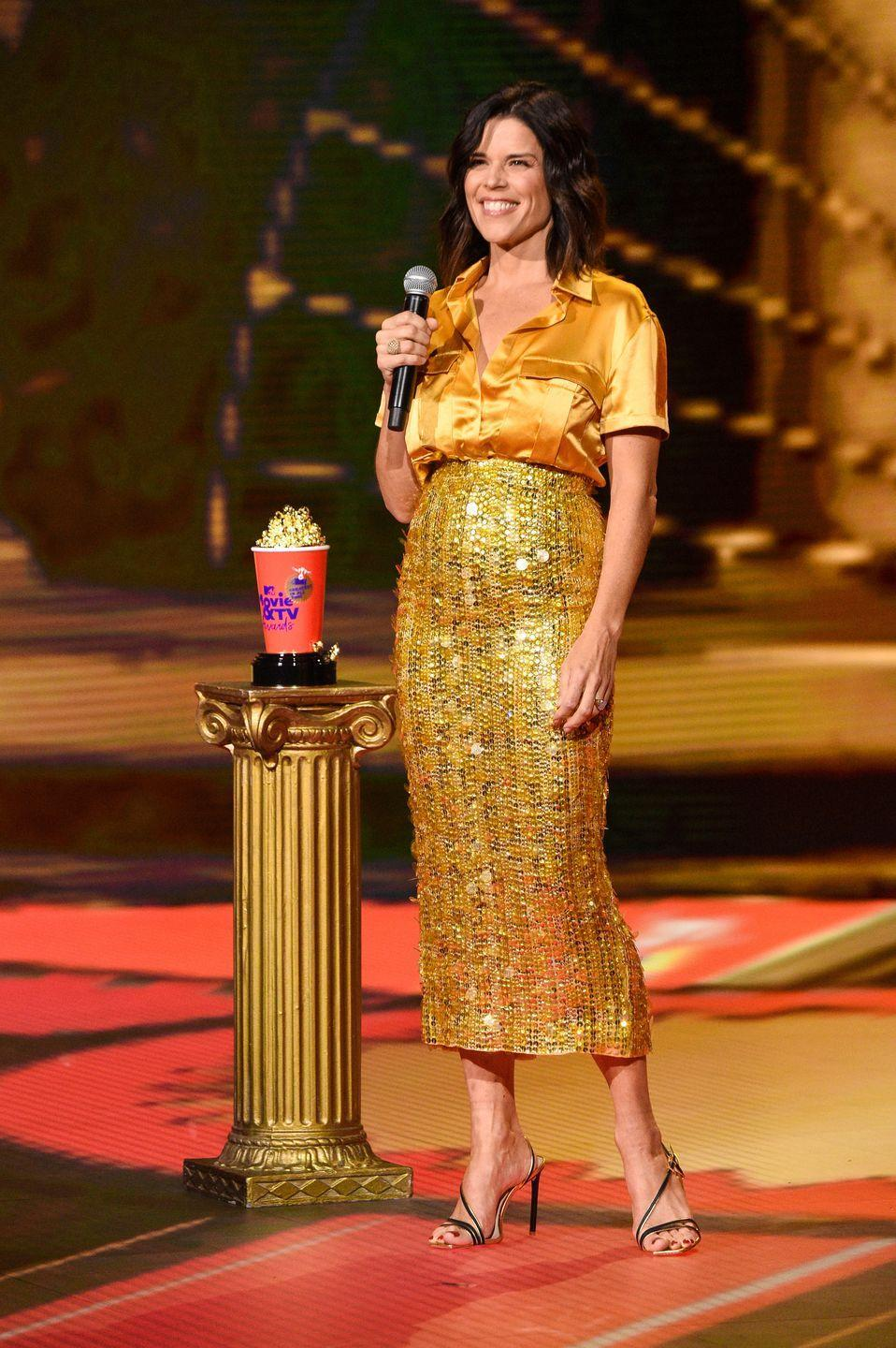 <p><strong>6 December </strong>Neve Campbell wore a sparkling gold pencil skirt and matching silk shirt, both by Aliette.</p>