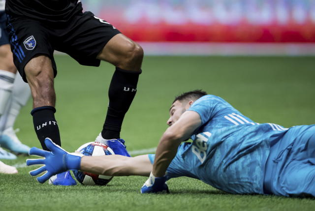 Vancouver Whitecaps goalkeeper Maxime Crepeau, right, dives for the ball at the feet of San Jose Earthquakes' Chris Wondolowski during the first half of an MLS soccer game, Saturday, July 20, 2019 in Vancouver, British Columbia. (Darryl Dyck/The Canadian Press via AP)