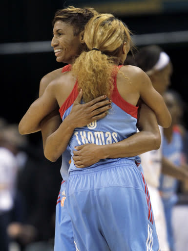 Atlanta's Angel McCoughtry, left, hugs teammate Alex Bentley in the closing seconds of the second half of Game 2 of the WNBA basketball Eastern Conference finals game against Indiana on Sunday, Sept. 29, 2013, in Indianapolis. Atlanta won 67-53 to advance to the finals. (AP Photo/AJ Mast)