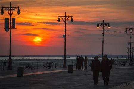 People walk at the Coney Island boardwalk during sunset on the one-year anniversary of Hurricane Sandy in the Brooklyn borough of New York