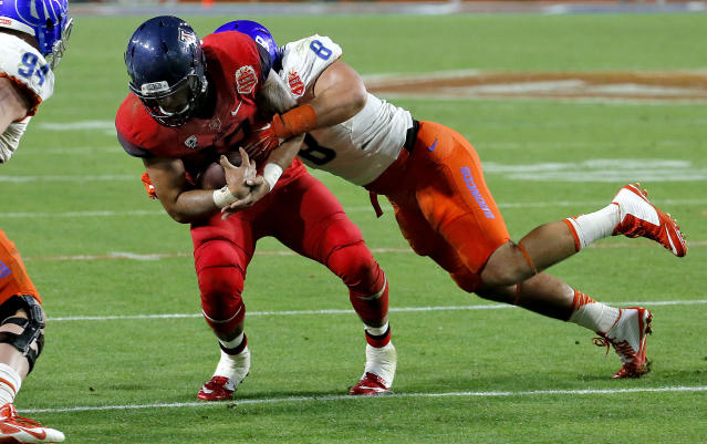 Boise State defensive lineman Kamalei Correa (8) tackles Arizona quarterback Anu Solomon (12) during the final seconds during the second half of the Fiesta Bowl NCAA college football game, Wednesday, Dec. 31, 2014, in Glendale, Ariz. Time expired before Arizona could run another play for a Boise State 38-30 win. (AP Photo/Matt York)