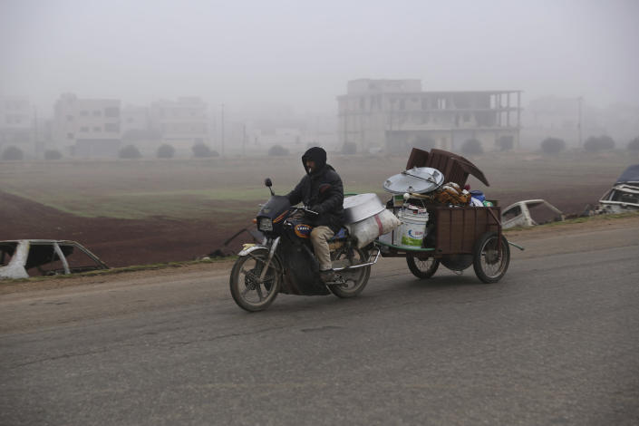 A man carries household goods on a motorbike while fleeing Maaret al-Numan, Syria, ahead of a government offensive, Monday, Dec. 23, 2019. (AP Photo/Ghaith al-Sayed)