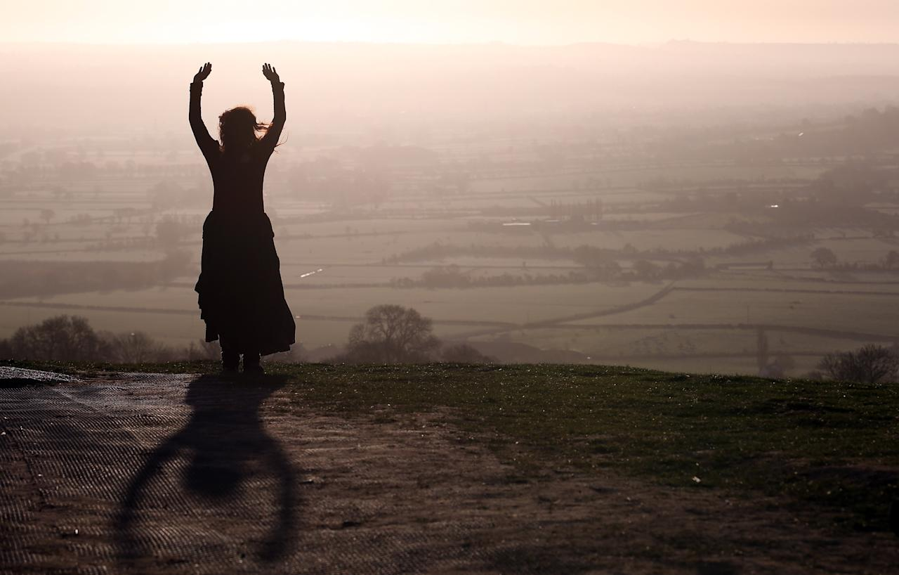 GLASTONBURY, ENGLAND - MAY 01:  A woman watches the sun rise during Beltane dawn celebration service in front of St. Michael's Tower on Glastonbury Tor on May 1, 2013 in Glastonbury, England. Although more synonymous with International Workers' Day, or Labour Day, May Day or Beltane is celebrated by druids and pagans as the beginning of summer and the chance to celebrate the coming of the season of warmth and light. Other traditional English May Day rites and celebrations include Morris dancing and the crowning of a May Queen with celebrations involving a Maypole.  (Photo by Matt Cardy/Getty Images)