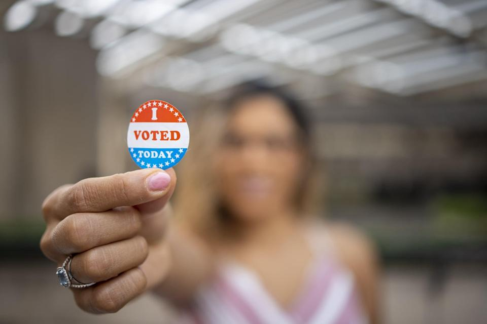A young Hispanic woman with her I voted sticker after voting in an election.