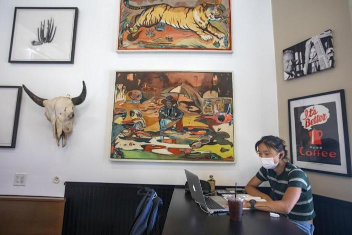 SOUTH PASADENA, CA - JULY 18: Lilian Zhu, 17, is working at her laptop wearing her face mask inside Charlie's Coffee House during the coronavirus pandemic on Sunday, July 18, 2021 in South Pasadena, CA. Once again the Los Angeles County on Sunday began requiring people to wear masks in indoor public places, opening a new battle line as the coronavirus is rising significantly among unvaccinated people. L.A. County is by far the biggest jurisdiction in the nation to require masks again. But with coronavirus cases rising across the nation largely because of the highly infectious Delta variant, officials elsewhere will be watching to see if the effort works. (Francine Orr / Los Angeles Times)