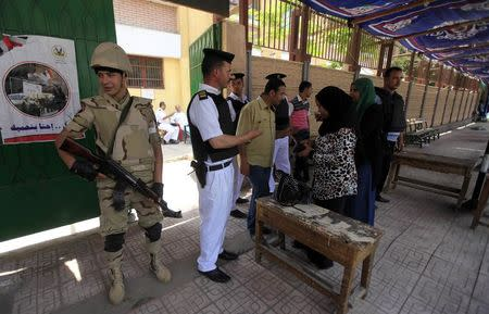 Voters present papers at polling station in El Sayda Zeinab area on third day of voting in Egyptian presidential elections in Cairo