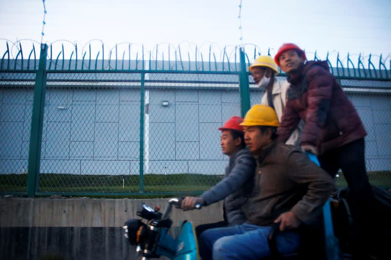 FILE PHOTO: Workers ride past the perimeter fence of what is officially known as a vocational skills education centre in Dabancheng