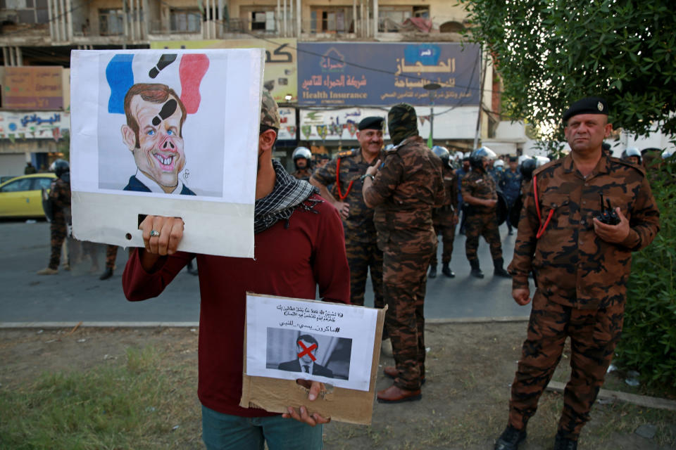 A protester holds defaced pictures of French President Emmanuel Macron during a protest over caricatures of the Prophet Muhammad they deem insulting and blasphemous, outside the French Embassy, in Baghdad, Iraq, Monday, Oct. 26, 2020. Muslims in the Middle East and beyond on Monday called for boycotts of French products and for protests over the caricatures, but France's president has vowed his country will not back down from its secular ideals and defense of free speech. (AP Photo/Khalid Mohammed)