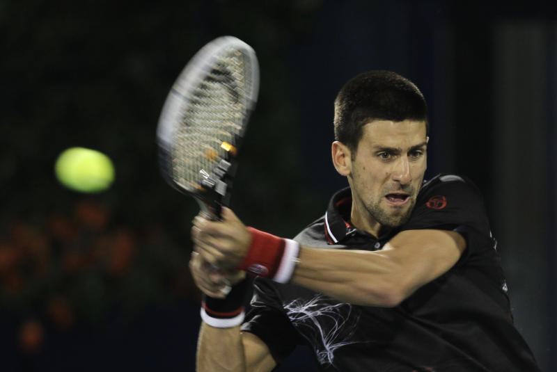 Novak Djokovic of Serbia returns the ball to Janko Tipsarevic of Serbia during a quarterfinal of the Emirates Dubai ATP Tennis Championships in Dubai, United Arab Emirates, Thursday, March 1, 2012. (AP Photo/Hassan Ammar)