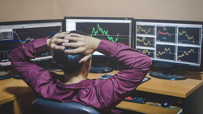 frustrated stock analyst looking at stock charts