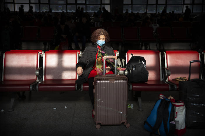 A traveler wears a face mask as she sits in a waiting room at Beijing West Railway Station in Beijing, Tuesday, Jan. 21, 2020. A fourth person has died in an outbreak of a new coronavirus in China, authorities said Tuesday, as more places stepped up medical screening of travelers from the country as it enters its busiest travel period. (AP Photo/Mark Schiefelbein)