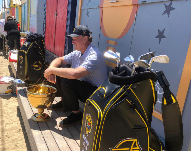 In this Nov. 26, 2018, file photo golfer Ernie Els, captain of the International Team at this year's Presidents Cup, sits in front of a beach house at Brighton in Melbourne, Australia. Royal Melbourne golf course will host the Presidents Cup in December for the third time, and is where the International Team won its only previous tournament against the United States in 1998. (AP Photo/Dennis Passa, FILE)