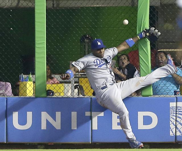 Los Angeles Dodgers right fielder Yasiel Puig is unable to catch a ball at the fence hit by Miami Marlins' Jeff Baker for a double, during the ninth inning of a baseball game, Sunday, May 4, 2014 in Miami. Adeiny Hechavarria scored on the play as the Marlins defeated the Dodgers 5-4. (AP Photo/Wilfredo Lee)