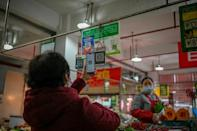 A woman uses her mobile phone to pay for produce at a market in Chengdu, the capital of China's Sichuan province