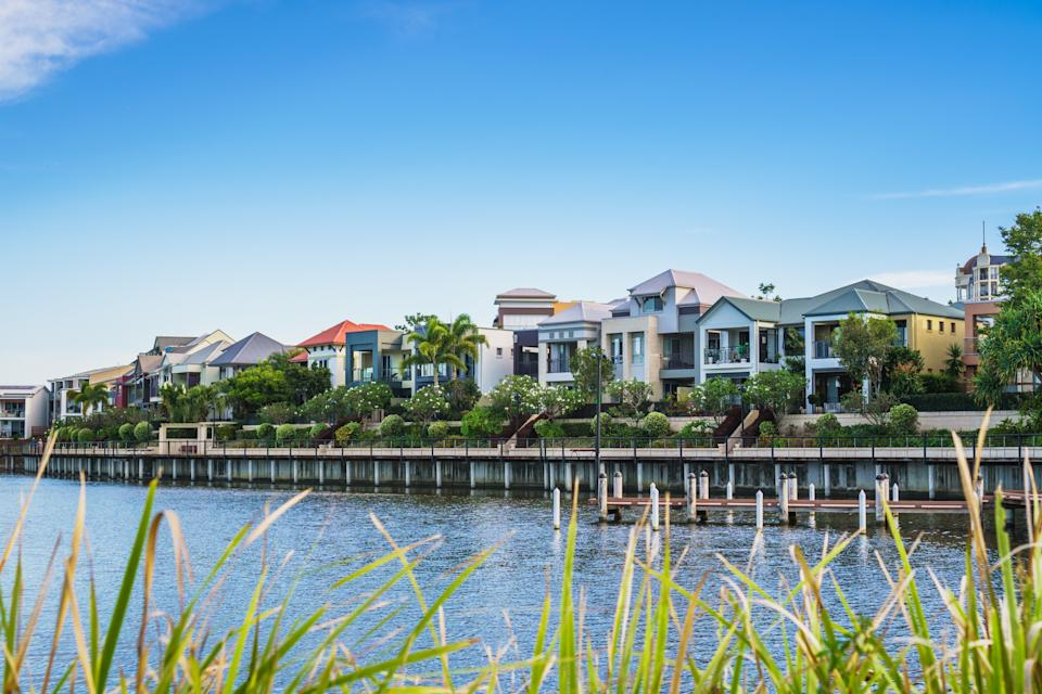 Wide panoramic view of Emerald Lakes residences across the lake, on a blue sky background during a beautiful sunset. Gold Coast, Australia.
