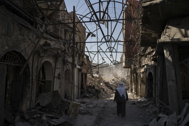 A man walks between destroyed shops in the Old City of Mosul, Iraq. (Photo: Felipe Dana/AP)