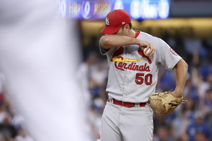 St. Louis Cardinals starting pitcher Adam Wainwright wipes his face