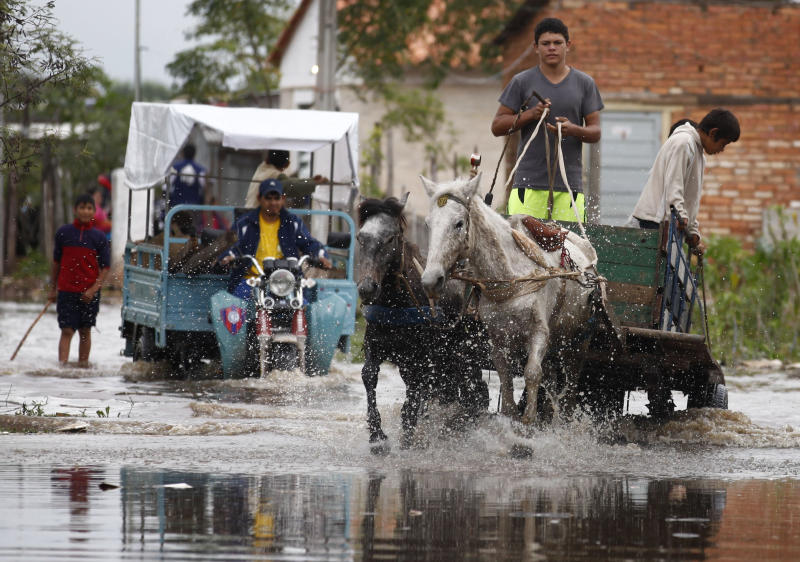 In this July 9, 2013 photo, a youth crosses a flooded road with a horse-drawn cart as a motorcyclist follows behind in the Santa Ana neighborhood of Asuncion, Paraguay. The city is phasing out the horse-drawn carts used by people who collect recyclable material and is sending the horses to an equine sanctuary. It's being funded by Maria Llorens, a wealthy Belgian landowner, who is using one of her ranches to give the horses shelter. (AP Photo/Jorge Saenz)