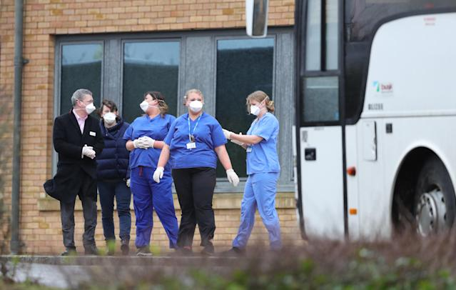 Staff wait as coaches carrying coronavirus evacuees arrive at Kents Hill Park Training and Conference Centre in Milton Keynes. (Getty)