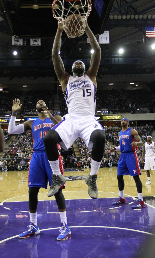Sacramento Kings center DeMarcus Cousins, center, dunks as Detroit Pistons' Greg Monroe, left, and Josh Smith, right, watch during the first quarter of an NBA basketball game in Sacramento, Calif., Friday, Nov. 15, 2013. (AP Photo/Rich Pedroncelli)