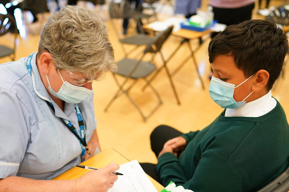 NEWCASTLE UPON TYNE, ENGLAND - SEPTEMBER 22: Felix Dima, 13, from Newcastle speaks with a nurse before he receives the Pfizer-BioNTech COVID-19 vaccine at the Excelsior Academy on September 22, 2021 in Newcastle upon Tyne, England.  The Excelsior Academy on Denton Road in Newcastle is the first school in the North East and North Cumbria to offer the Pfizer-BioNTech COVID-19 vaccination to healthy 12-15-year-olds where parents have provided consent. This week the NHS and local School Age Vaccination Services begin immunising children aged 12 to 15 on advice from the UK's four Chief Medical Officers, in a move to reduce the disruption to education caused by COVID-19. The Medicines and Healthcare products Regulatory Agency (MHRA) confirmed that the Pfizer vaccine is safe and effective for 12 to 17-year-olds. (Photo by Ian Forsyth/Getty Images)