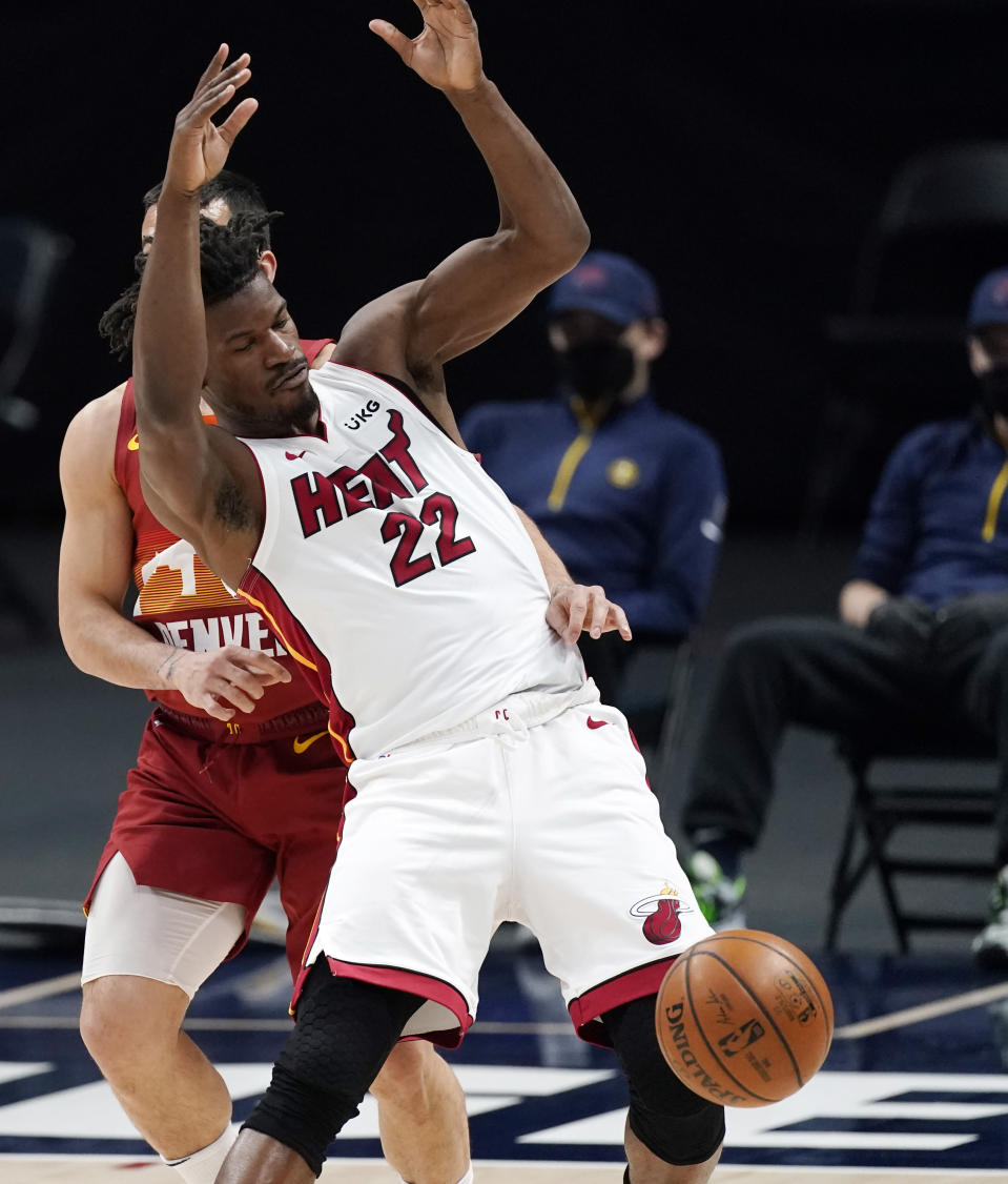 Miami Heat forward Jimmy Butler, front, is fouled by Denver Nuggets guard Facundo Campazzo during the first half of an NBA basketball game Wednesday, April 14, 2021, in Denver. (AP Photo/David Zalubowski)