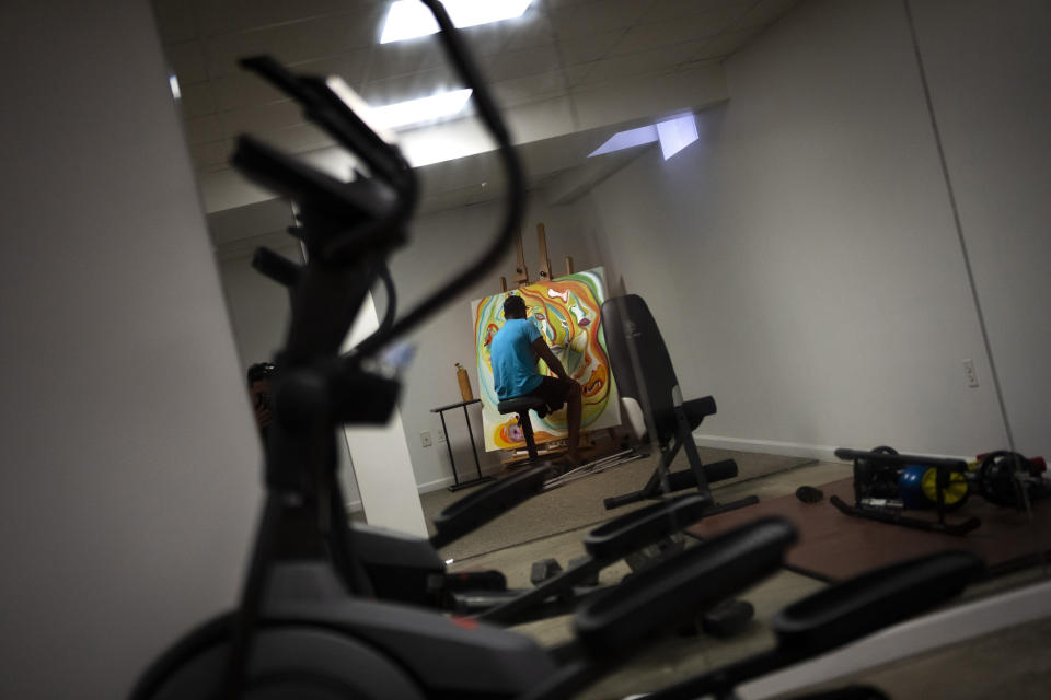 """Freddie De Los Santos paints a canvas in his basement in Hopewell Junction, N.Y., on Wednesday, Aug. 19, 2021. """"I have days where you see me moving and laughing, but I'm not functioning very well,"""" he says. """"But I'm still pushing forward."""" (AP Photo/Emilio Morenatti)"""