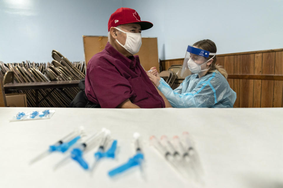 """Mario Valdez, 62, receives his first shot of a vaccine at a clinic in Central Falls, R.I., Saturday, Jan. 9, 2021. """"I feel happy,"""" the 62-year-old school bus driver said shortly after receiving his second and final dose five weeks later. """"Too many people here have COVID. It's better to be safe."""" (AP Photo/David Goldman)"""