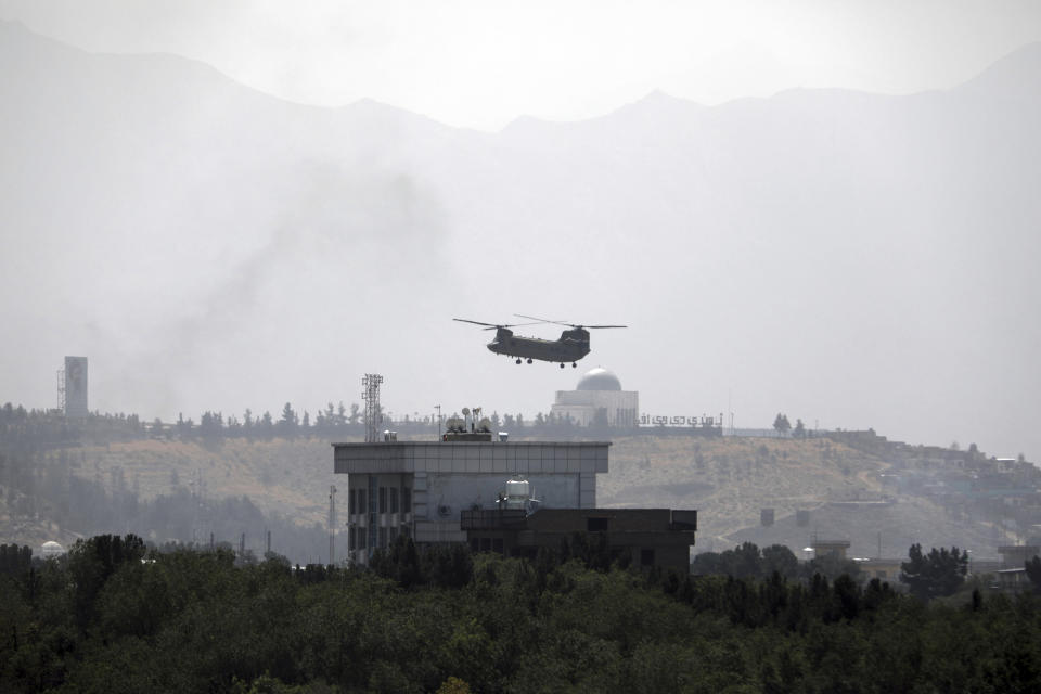 FILE - In this Aug. 15, 2021 file photo, a U.S. Chinook helicopter flies over the U.S. embassy in Kabul, Afghanistan. Helicopters are landing at the embassy as diplomatic vehicles are leaving the compound amid the Taliban advance on the Afghan capital. (AP Photo/Rahmat Gul, File)