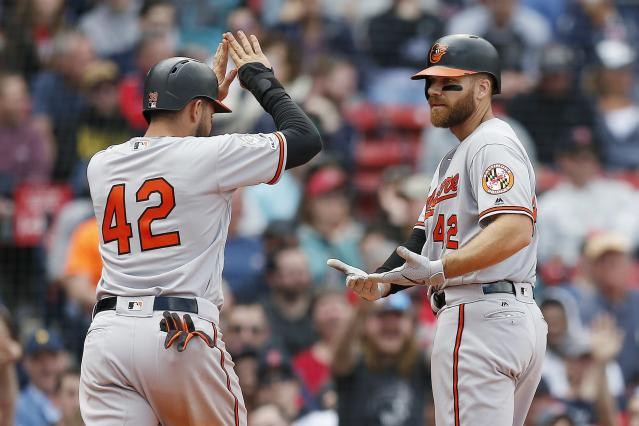 Baltimore Orioles' Chris Davis, right, celebrates his two-run home run that also drove in Renato Nunez, left, during the eighth inning of a baseball game against the Boston Red Sox in Boston, Monday, April 15, 2019. (AP Photo/Michael Dwyer)