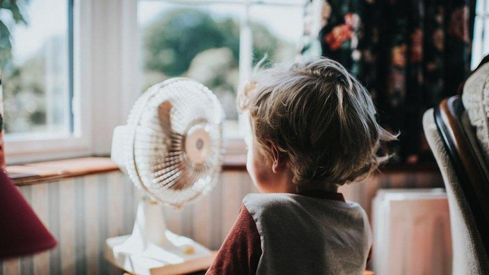 A photo of child in front of a window and an electric fan