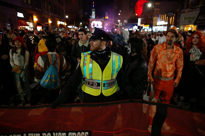 NYPD officers stand guard during the Halloween parade hours after a man driving a rental truck struck and killed eight people in lower Manhattan.