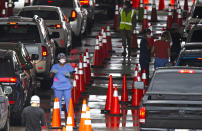 Vehicles line up as healthcare workers help to check-in as citizens are being tested at the COVID-19 drive-thru testing center at Hard Rock Stadium in Miami Gardens on Sunday, Nov. 22, 2020. (David Santiago/Miami Herald via AP)