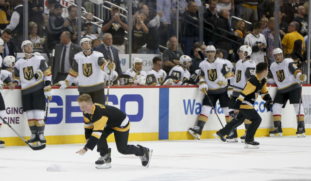 Pittsburgh Penguins ice crew members pick up hats on the ice as the Vegas Golden Knights lean along the boards after Penguins' Phil Kessel scored his third goal of the night, during the second period of an NHL hockey game, Thursday, Oct. 11, 2018, in Pittsburgh. (AP Photo/Keith Srakocic)