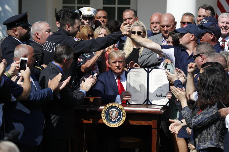 President Trump holds up the signed bill permanently reauthorizing the September 11th Victim Compensation Fund in the Rose Garden of the White House on Monday. (AP Photo/Alex Brandon)