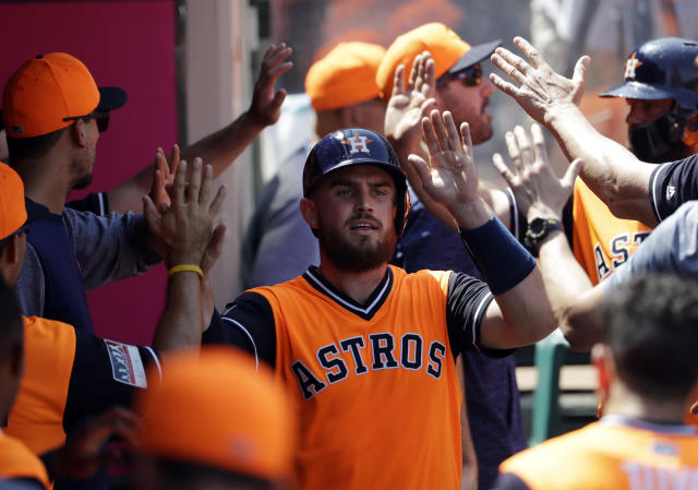 Houston Astros' Max Stassi is high-fived in the dugout after scoring on a single from Carlos Correa during the third inning of a baseball game Sunday, Aug. 26, 2018, in Anaheim, Calif. (AP Photo/Marcio Jose Sanchez)