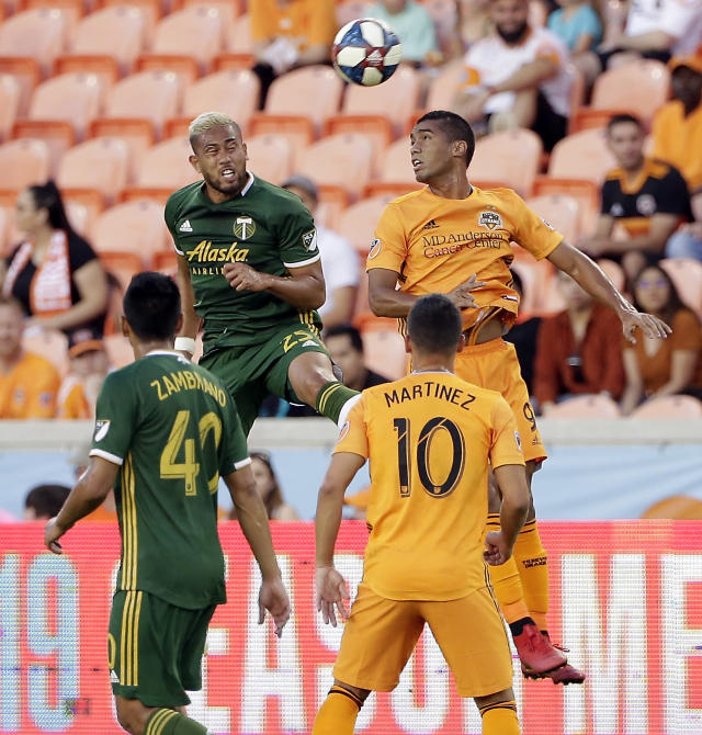 Portland Timbers defender Bill Tuiloma (25) and Houston Dynamo forward Mauro Manotas (9) go up for a header in front of Portland midfielder Renzo Zambrano (40) and Houston midfielder Tomas Martinez (10) during the first half of an MLS soccer match Wednesday, May 15, 2019, in Houston. (AP Photo/Michael Wyke)