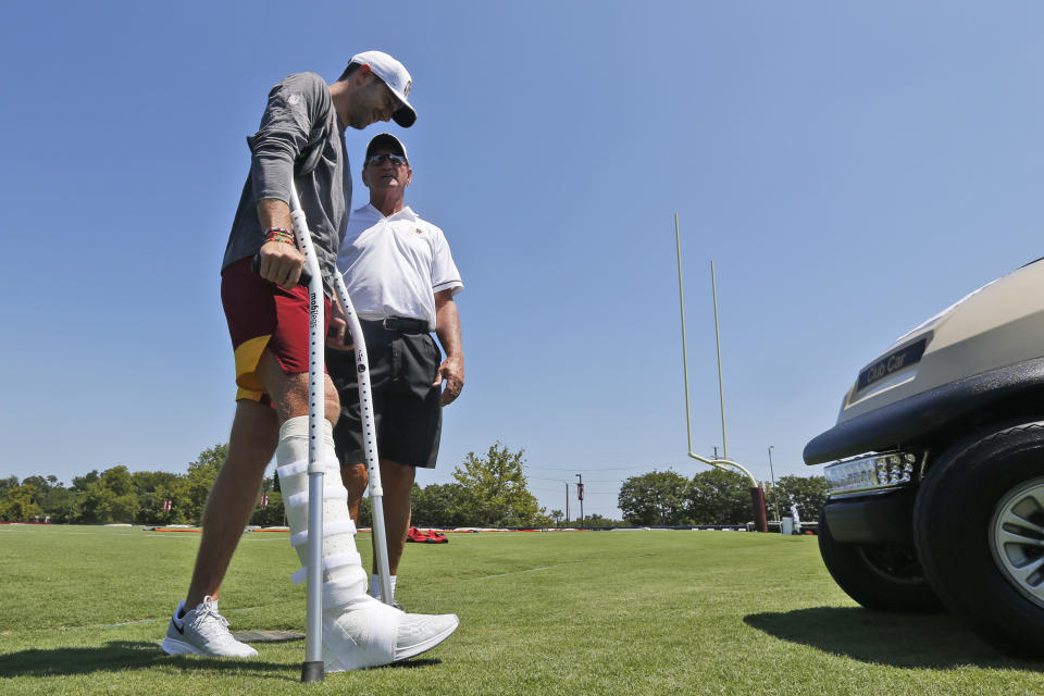 Alex Smith, left, walks to a cart as he talks with former Redskins quarterback Joe Theismann at a practice in July of 2019. (AP Photo/Steve Helber)